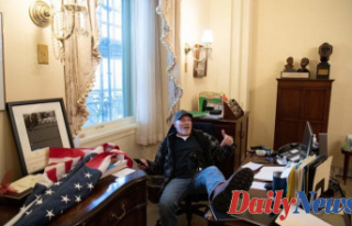 Capitol rioter sitting in Mind Congressional chair...
